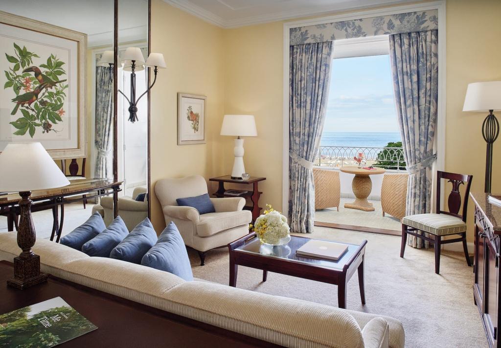 Salon avec une chambre à coucher avec table et fauteuils sur le balcon, au Belmond Copacabana Palace (RJ)