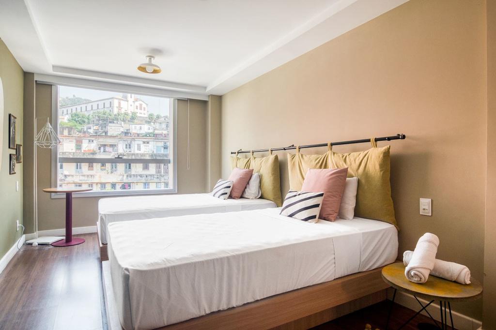 Chambre de Selina Lapa avec deux lits, grande fenêtre, murs, tête de lit et table d'appoint en beige