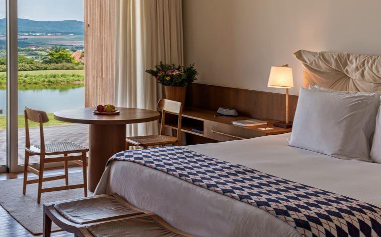 Chambre d'hôtel Fasano Boa Vista, avec grand lit, table et deux chaises, donnant sur un lac et les montagnes