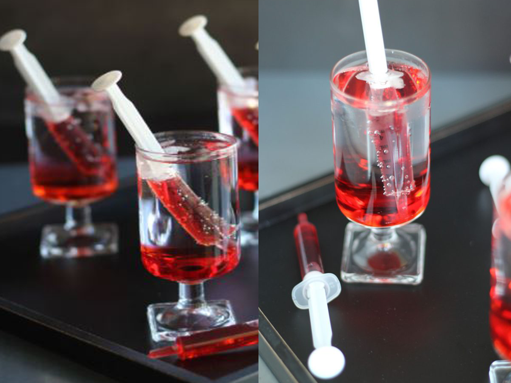 Verres avec de l'eau pétillante et une seringue en plastique avec un liquide rouge à l'intérieur