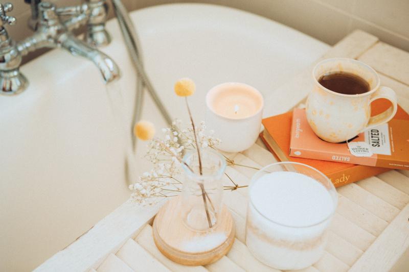 Bougies, fleurs, livres et une tasse de thé sur un support en bois dans une baignoire