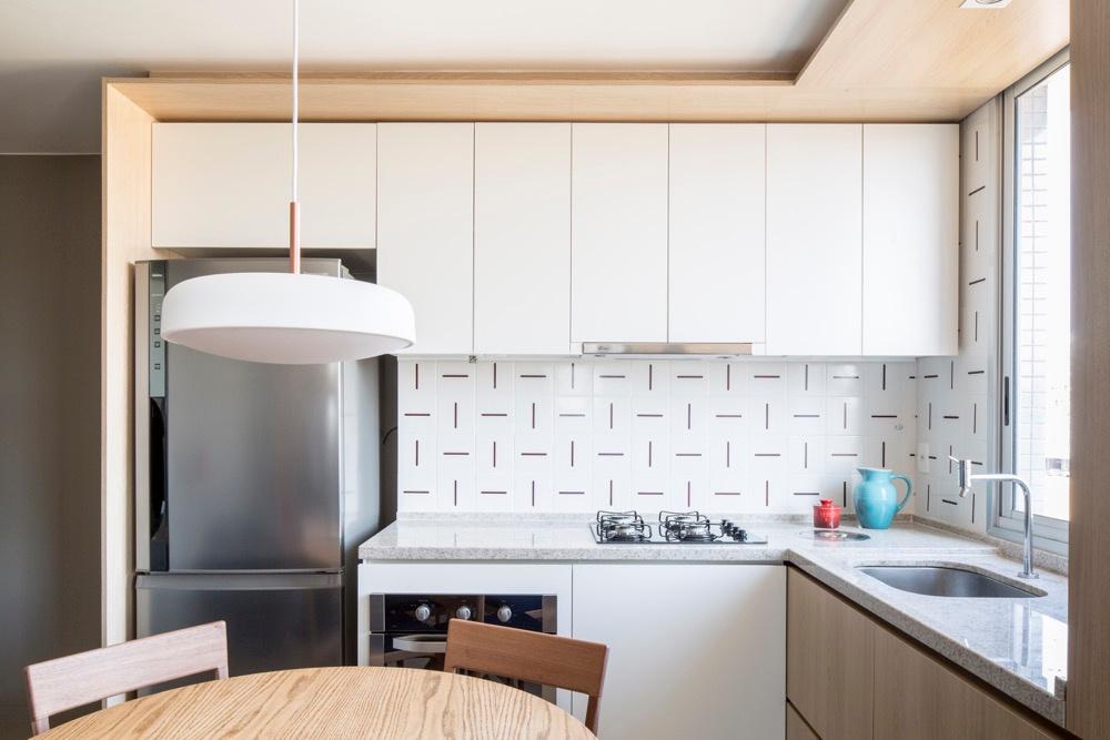 Cuisine avec armoires blanches et carreaux à motifs dans petit appartement