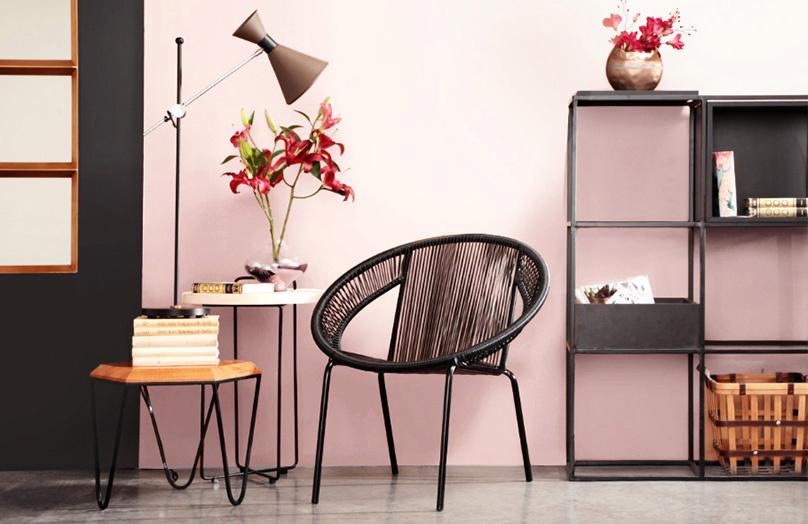 Environnement avec chaise tressée noire, deux tables d'appoint, l'une avec des fleurs roses et l'autre avec une lampe.  Étagère noire en arrière-plan.  Mur rose clair