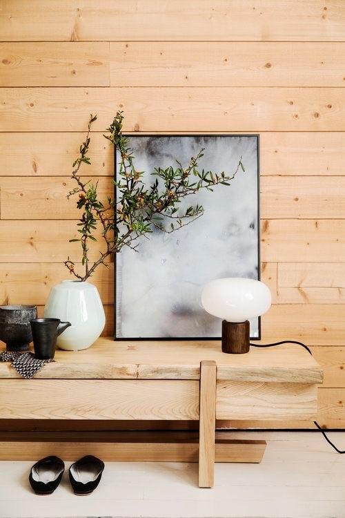 Hack en bois avec mur en bois en arrière-plan.  Cadre gris et blanc soutenu par le hack.  Petite lampe devant le cadre.  Vase avec branche feuillue à gauche à côté d'un service à thé de style japonais
