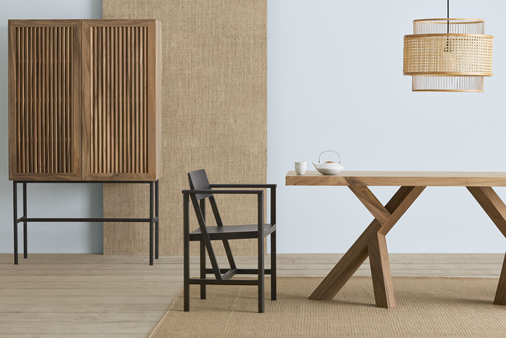 Salle à manger en bois avec table et chaise en bois noir.  Lampe tressée en fibre ci-dessus.  Étagères à litière à lattes en bas