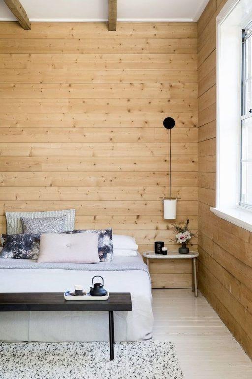 Chambre avec mur en bois et lit double blanc avec quatre oreillers.  Petite suspension sur le côté droit comme lampe