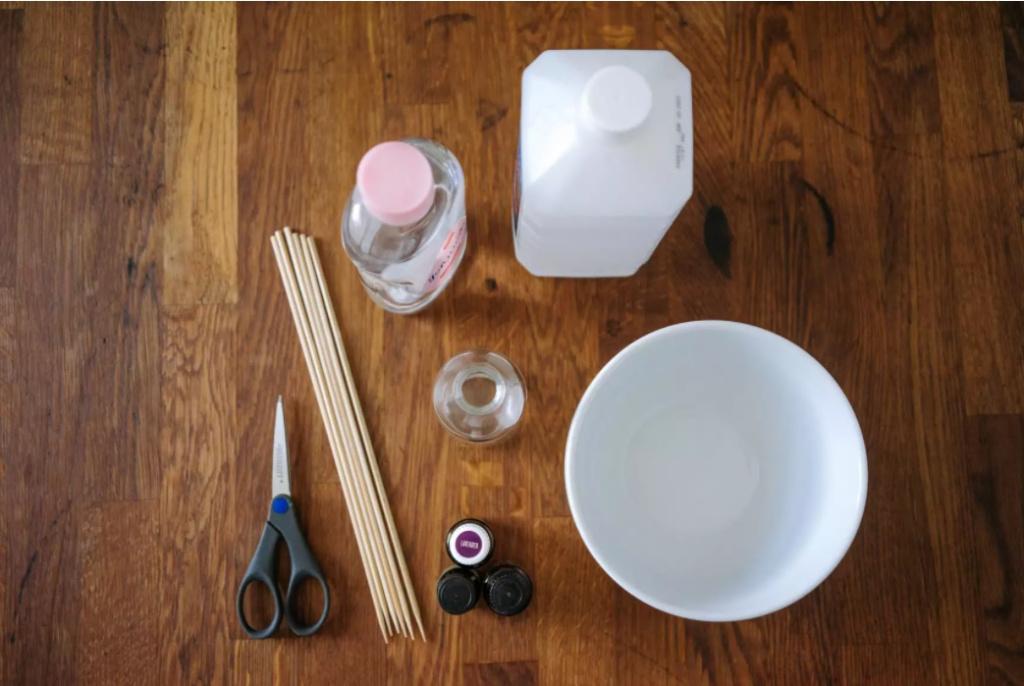 Table en bois avec des produits pour faire des arômes.  Ciseaux, bâtons, alcool, bol, bouteille en verre et huiles.  Tout vu d'en haut.