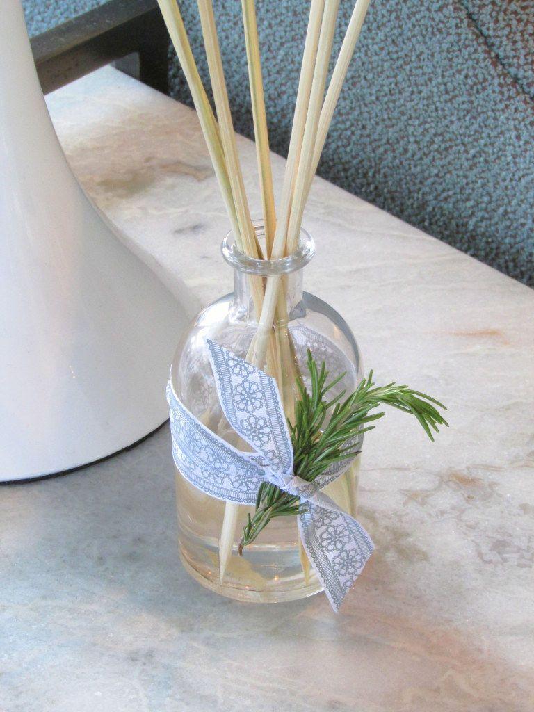 Diffuseur avec bouteille transparente et bâtonnets en bois.  Ruban violet noué au milieu du pot avec une branche de romarin coincée dedans