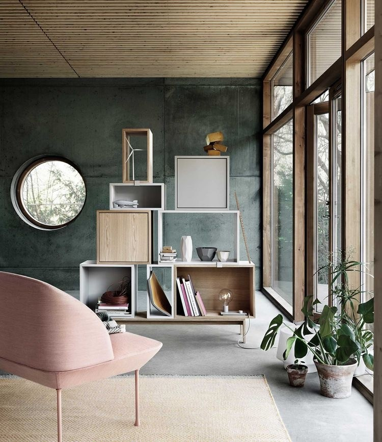 Chambre avec mur brûlé vert et fenêtre.  Fauteuil rose clair au premier plan et étagères de niche en bois empilées à l'arrière-plan