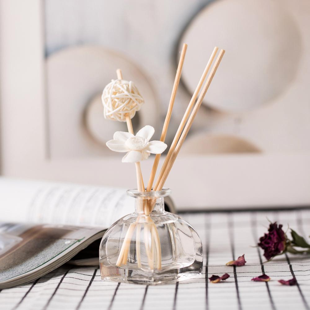 Flacon en verre aromatisant avec base carrée et côtés arrondis sur une serviette blanche avec motif en damier noir.  Trois bâtons en bois sortant du pot.  Un bâton avec une fleur blanche et un avec une boule blanche.