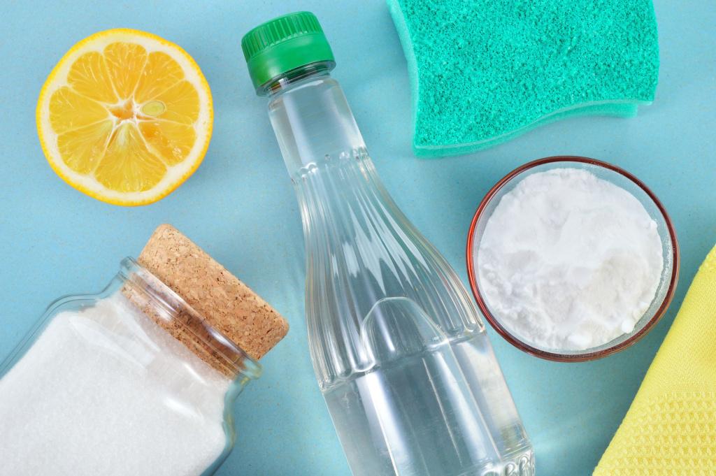 Fond bleu avec bouteille de liquide clair, bicarbonate de soude, éponge et citron