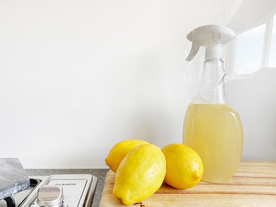 Flacon pulvérisateur transparent avec liquide jaunâtre, avec trois citrons sur le côté sur un banc en bois