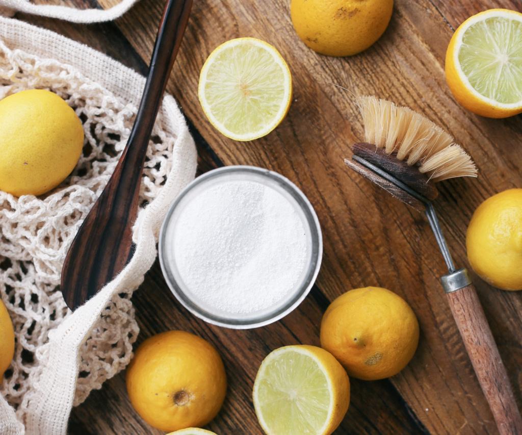 bicarbonate de soude, citrons et brosse en bois sur un banc en bois