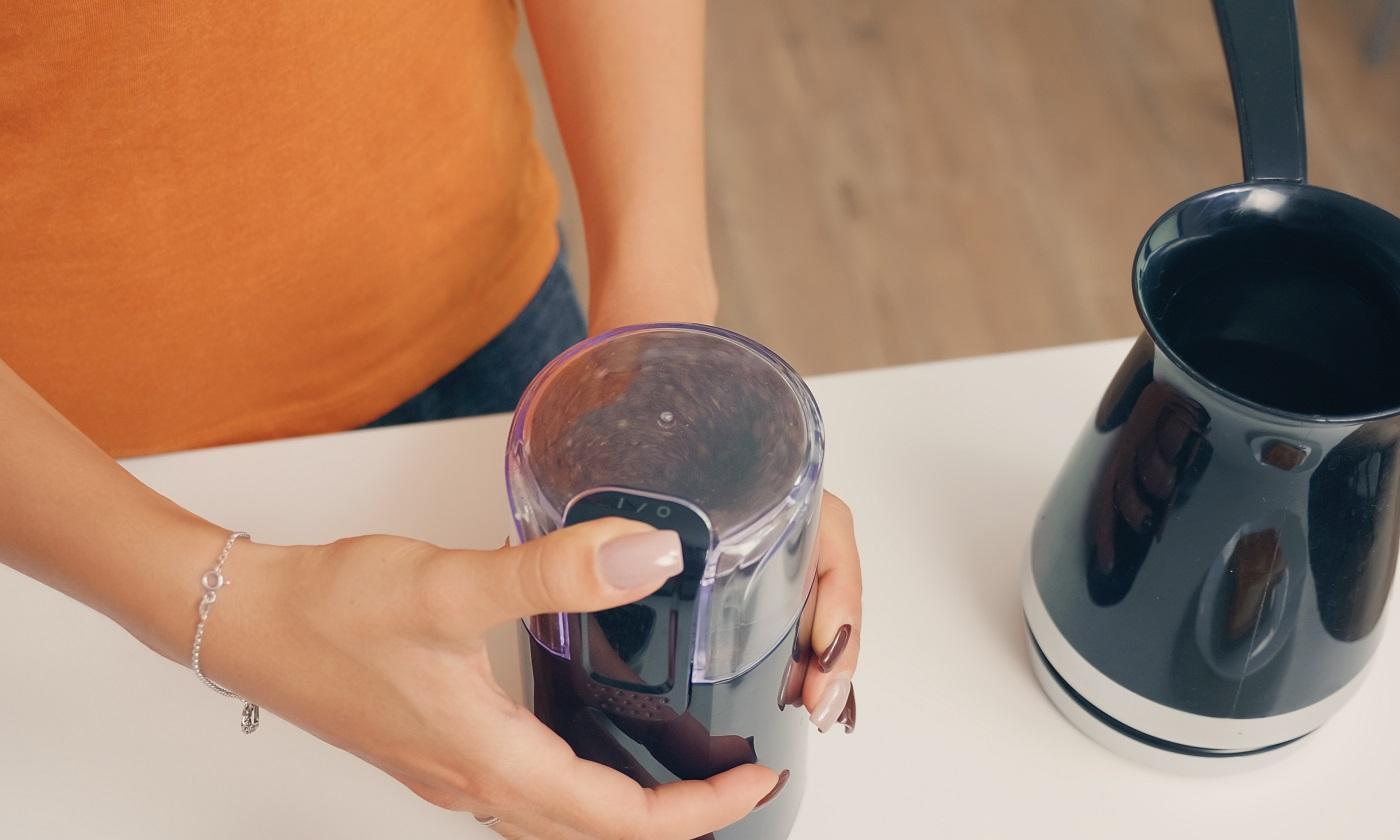 Femme moulant des grains de café torréfiés.  Femme au foyer à la maison faisant du café moulu frais dans la cuisine pour le petit déjeuner, boire, moudre du café expresso avant d'aller travailler