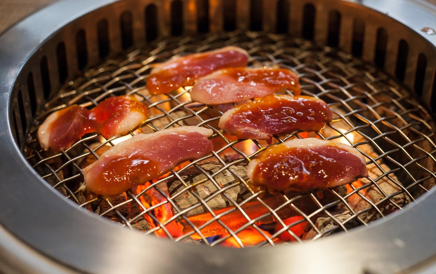 rôtir de la viande de canard et des légumes sur une poêle à griller en morceaux de charbon de bois naturel rougeoyant et flamboyant dans un restaurant de nourriture barbecue grill poêle arrière-plan.