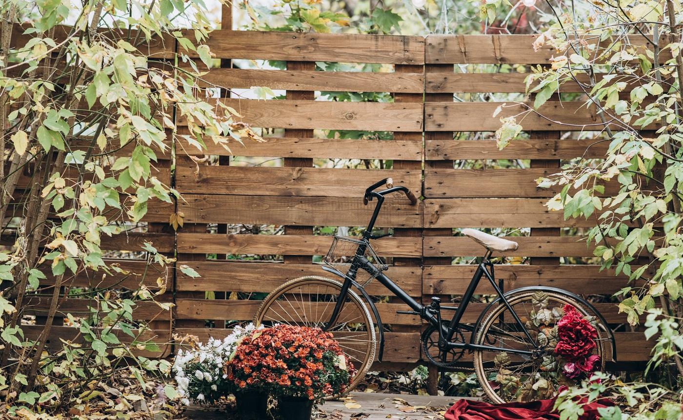 Clôture en bois vintage recouverte de feuilles d'automne et d'un vélo debout à proximité dans la cour d'automne.  Notion de saisons.  Stock photo